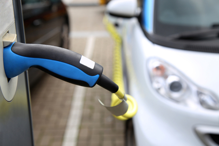 Electric car being charged at the station, close up of the power supply plugged