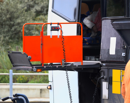 chair on the lift: details of a bus using a chair lift for wheelchair