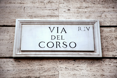 street signs: Via del Corso sign on building wall in Rome, Italy