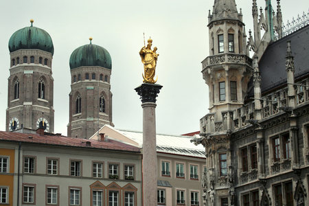 bayern old town: The Golden statue of Mary (Mariensaule), a Marian column on the Marienplatz, Frauenkirche in the background in Munich, German