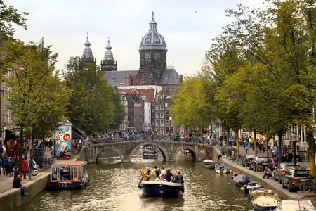 nicolaas: AMSTERDAM, THE NETHERLANDS - AUGUST 18, 2015: View on Saint Nicholas church or St Nicolaas kerk tower from Oudekennissteeg bridge. Street life, Canal, tourists and boat in Amsterdam. Amsterdam is capital of the Netherlands on August 18, 2015.