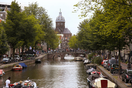 nicolaas: AMSTERDAM, THE NETHERLANDS - AUGUST 16, 2015: View on Saint Nicholas church or St Nicolaas kerk tower from Oudekennissteeg bridge. Street life, Canal, tourists and boat in Amsterdam. Amsterdam is capital of the Netherlands on August 16, 2015.