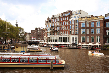 amstel: AMSTERDAM, THE NETHERLANDS - AUGUST 19, 2015: View on Hotel de lEurope and Amstel street from Halvemaansbrug. Street life, Canal, bicycle and boat in Amsterdam. Amsterdam is capital of the Netherlands on August 19, 2015.