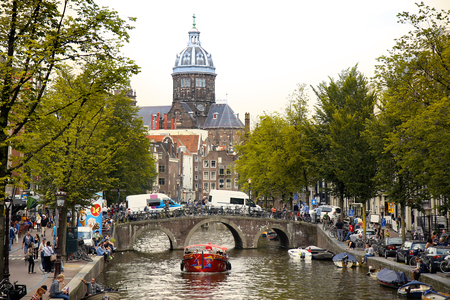 nicolaas: AMSTERDAM, THE NETHERLANDS - AUGUST 19, 2015: View on Saint Nicholas church or St Nicolaas kerk tower from Oudekennissteeg bridge. Street life, Canal, tourists and boat in Amsterdam. Amsterdam is capital of the Netherlands on August 19, 2015.