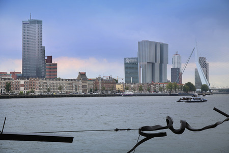 nederland: ROTTERDAM, THE NETHERLANDS - 18 AUGUST: Rotterdam is a city modern architecture, view on Erasmus Bridge (Erasmusbrug) and skyline of Rotterdam with a cruise boat, river Maas in Rotterdam, Netherlands on August 18,2015.
