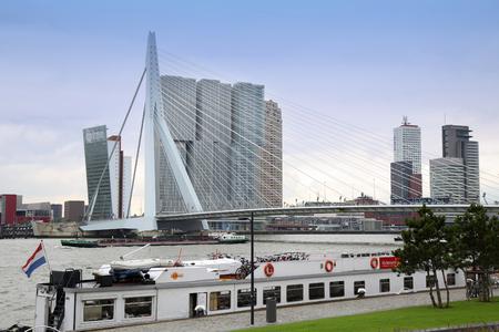 maas: ROTTERDAM, THE NETHERLANDS - 18 AUGUST: Rotterdam is a city modern architecture, view on Erasmus Bridge (Erasmusbrug) and skyline of Rotterdam with a cruise boat, river Maas in Rotterdam, Netherlands on August 18,2015.