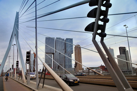 bicyclists: ROTTERDAM, THE NETHERLANDS - 18 AUGUST: Rotterdam is a city modern architecture. Cars traffic driving and bicyclists crossing on the Erasmus bridge (Erasmusbrug) in Rotterdam, Netherlands on August 18,2015.