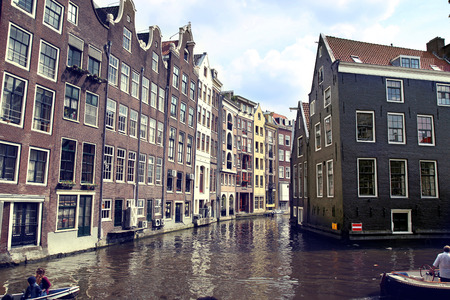 canal street: AMSTERDAM, THE NETHERLANDS - AUGUST 19, 2015: View on Oudezijds Kolk canal, street life, bicycle, canal in Amsterdam. Amsterdam is capital of the Netherlands on August 19, 2015. Editorial