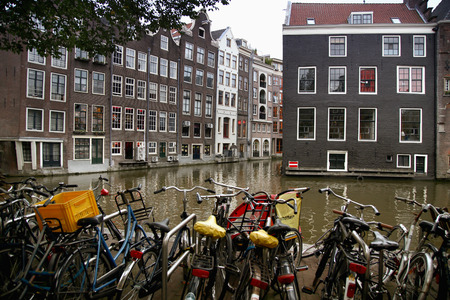 nicolaas: AMSTERDAM, THE NETHERLANDS - AUGUST 18, 2015: View on Oudezijds Kolk canal, street life, bicycle, canal in Amsterdam. Amsterdam is capital of the Netherlands on August 18, 2015.