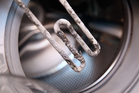 limescale: details closeup shot of electric heater from washing machine Stock Photo