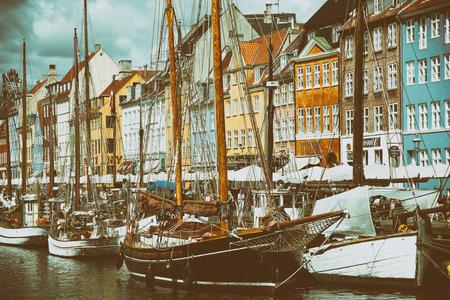 COPENHAGEN, DENMARK - AUGUST 14, 2016: Boats in the docks Nyhavn, people, restaurants and colorful architecture. Nyhavn a 17th century harbour in Copenhagen, Denmark on August 14, 2016.