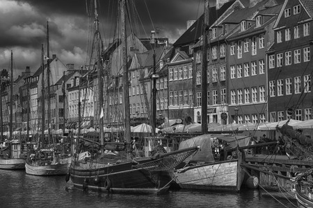 COPENHAGEN, DENMARK - AUGUST 14, 2016: Black and white photo, boats in the docks Nyhavn, people, and colorful architecture. Nyhavn a 17th century harbour in Copenhagen, Denmark on August 14, 2016.