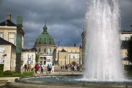 frederik: COPENHAGEN, DENMARK - AUGUST 15, 2016: A fountain in the Amalie Garden, with many tourist, in the background is Frederiks Church and Sculpture of Frederik V in Copenhagen, Denmark on August 15, 2016.