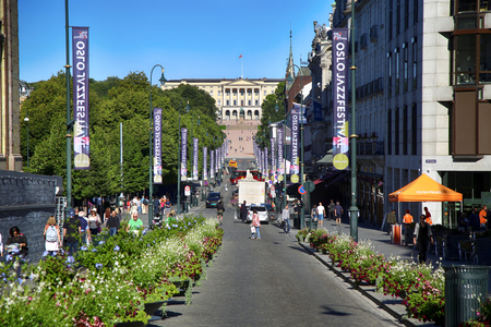 OSLO, NORWAY - AUGUST 18, 2016: People walk Oslos main street Karl Johans at center with the Royal Palace in the background in Oslo, Norway on August 18, 2016. Editorial