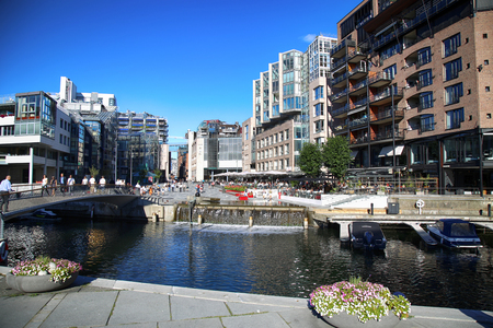 lux: OSLO, NORWAY – AUGUST 17, 2016: People walking on wonderful modern residential district Aker Brygge with lux apartments, shopping, culture and restaurants in Oslo, Norway on August 17,2016.
