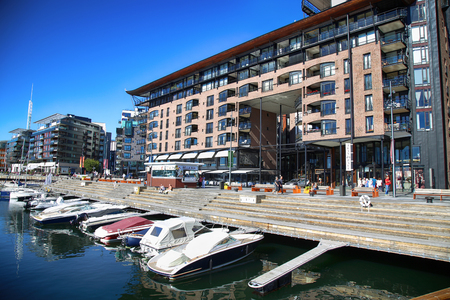 OSLO, NORWAY – AUGUST 17, 2016: People walking on modern district on street Stranden, Aker Brygge district with lux apartments, shopping, culture and restaurants in Oslo, Norway on August 17,2016.