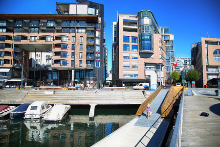 lux: OSLO, NORWAY – AUGUST 17, 2016: People walking on modern district on street Stranden, Aker Brygge district with lux apartments, shopping, culture and restaurants in Oslo, Norway on August 17,2016.
