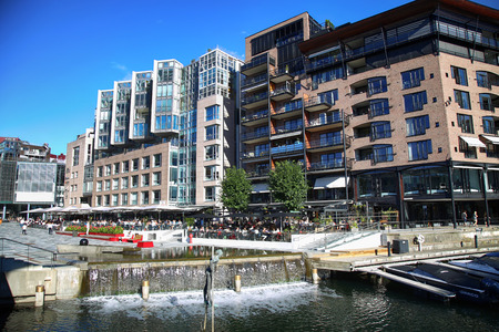 OSLO, NORWAY – AUGUST 17, 2016: People walking on wonderful modern residential district Aker Brygge with lux apartments, shopping, culture and restaurants in Oslo, Norway on August 17,2016. Editorial