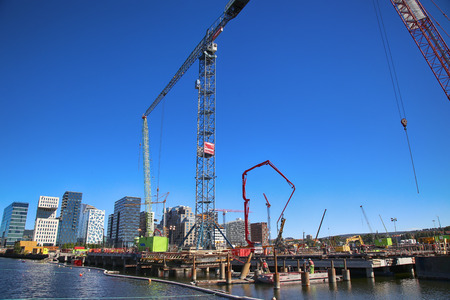 construction vehicle: OSLO, NORWAY – AUGUST 17, 2016: A construction site of Bjorvika under construction in progress with a heavy vehicle and cranes in Oslo, Norway on August 17,2016.