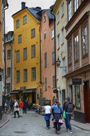 stan: STOCKHOLM, SWEDEN - AUGUST 19, 2016: View of narrow street and colorful buildings in Gamla Stan, tourists walk and visit on Gamla Stan, old town in central Stockholm, Sweden on August 19, 2016.