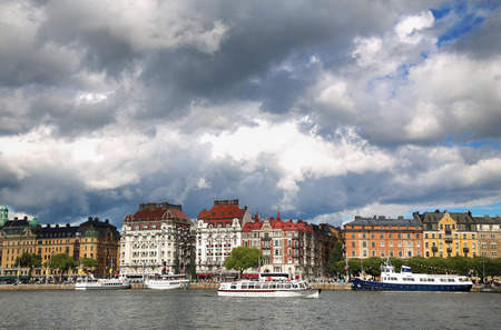 distric: STOCKHOLM, SWEDEN - AUGUST 20, 2016: Many people walk and visit on Strandvagen street on Ostermalm distric with touristic sightseeing boats in Stockholm, Sweden on August 20, 2016.