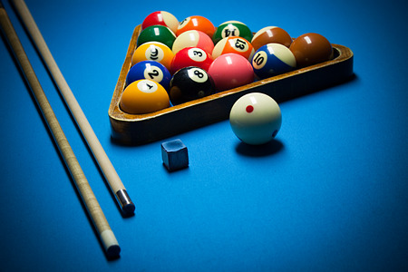 Image of billiard balls, cue and chalk on blue table.