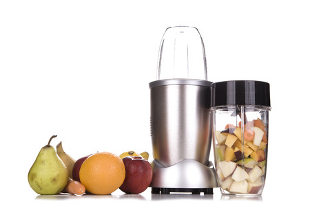 Healthy fruits with small blender on a cutting board getting ready for making a smoothie in a kitchen setting..