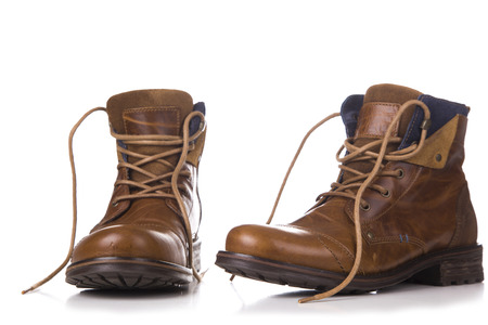 a pair of worn brown boots isolated on a white background