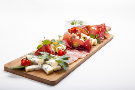 Antipasto platter cold meat plate with bread sticks, prosciutto, slices ham, beef jerky, meats, sausages, salami, ham, olives, laid and arugula on cutting board on wooden background. Meat appetizer. Stock Photo - 94311627