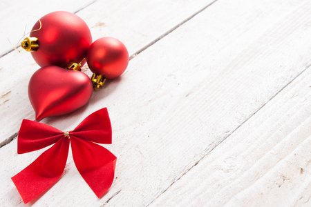Red Christmas decorations and bow on a wooden background. Stock Photo