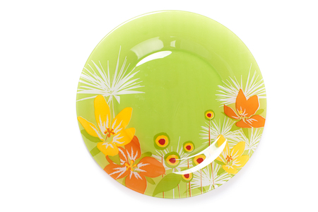 Green plate with flowers in color isolated on white