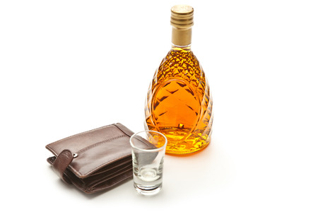 Glass bottle of brandy wallet and small glass.