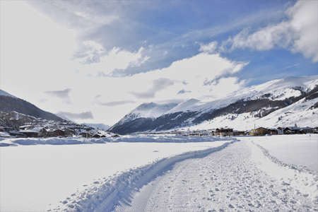 Winter scenery in the Alpine village Livigno, with the cross country ski track on the foreground and the village in the background 写真素材