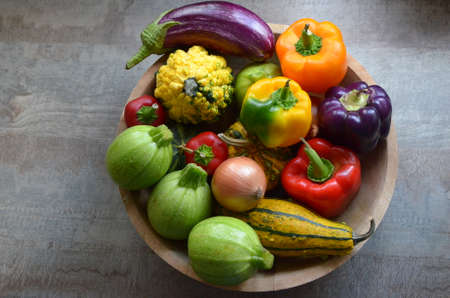 A wooden bowl with fresh organic autumn vegetables: zucchinis, pumpkins, red, orange and purple paprika, onions, eggplant