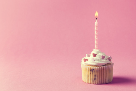 lighted: One nicely decorated muffin with cream, sprinkles and lighted birthday candle isolated on pink background Stock Photo