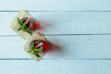 organic raspberry: Top view of two jars with organic raspberry juice, with striped red and white drinking straws and fresh mint leaves in it, placed on burlap coasters on wooden boards surface