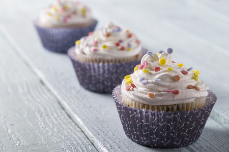 cup cakes: Three cup cakes with colorful sprinkles on a wooden table Stock Photo
