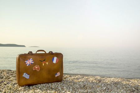 peacefull: Vintage suitcase with flag stickers placed on the beach with peacefull sea during sunrise on Thassos island in Greece
