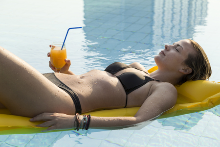 matress: Young, attractive blond woman laying down on a floating matress, holding a glass of an orange juice