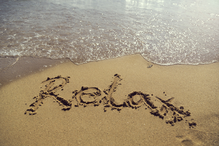waterline: Word relax handwritten in golden sand on the beach next to the waterline Stock Photo