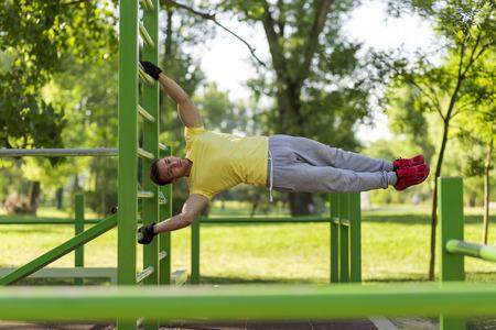 스트레칭 운동을 하 고 야외 체육관에서 밖으로 작동하는 젊은 선수
