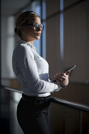 authoritative woman: Strong, confident, business woman standing in an office building, holding tablet computer