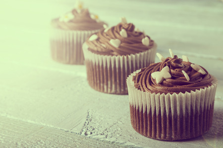 nicely: Close up of a nicely decorated chocolate cupcake on a wooden background