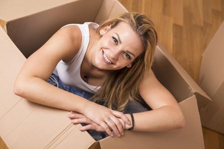 carton: La mujer se sienta dentro de una caja de cartón mientras que el embalaje