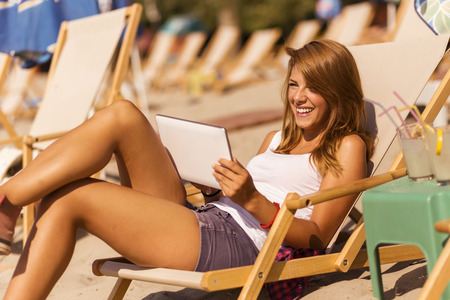 Attractive brunette lying on a sunbed on a beach and reading an e-book on a tablet computer