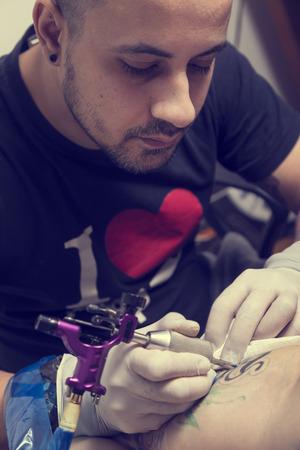 tattoo arm: Male tattoo artist holding a tattoo gun, showing a process of making tattoos on a male tattooed models arm. Focus on tattoo artists eyes