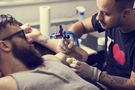 holding in arm: Male tattoo artist holding a tattoo gun, showing a process of making tattoos on a male tattooed models arm.