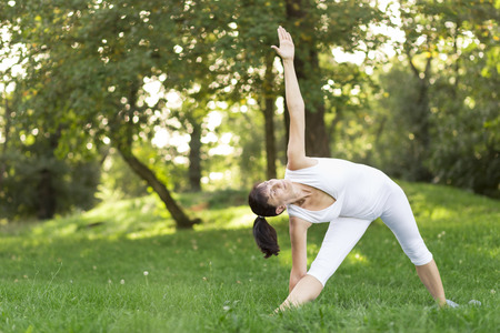 outdoor exercise: Middle aged woman doing yoga early in the morning in a park