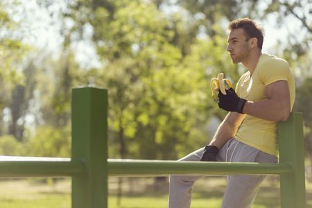 Young sportsman sitting on a bar in an outdoor gym, eating a banana