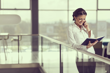 authoritative woman: Young successful business woman speaking on a mobile phone
